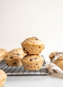 Two chocolate muffins stacked on a cooling rack.