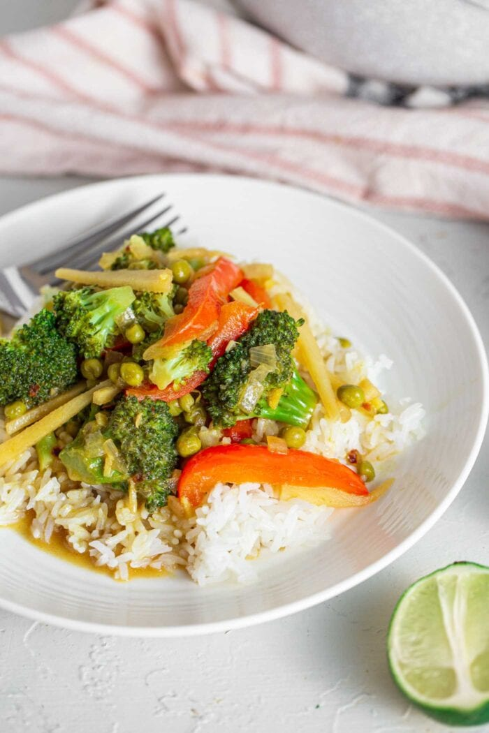 A bowl of green curry over rice.