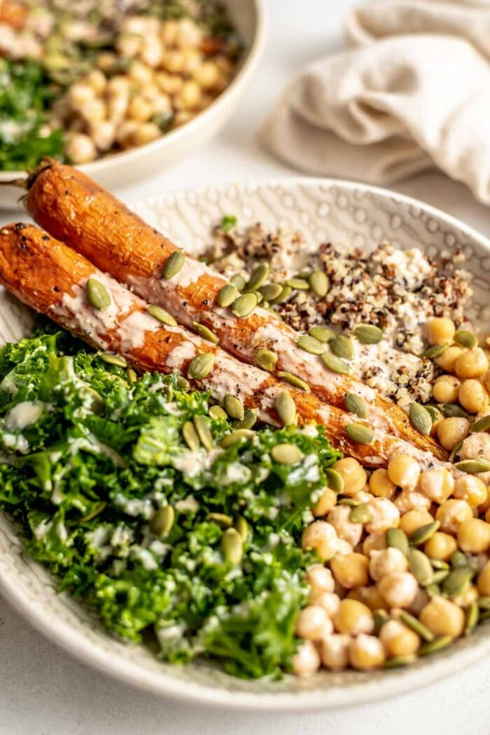 Roasted carrots, kale, quinoa, chickpeas and pumpkin seeds in a bowl topped with tahini sauce.
