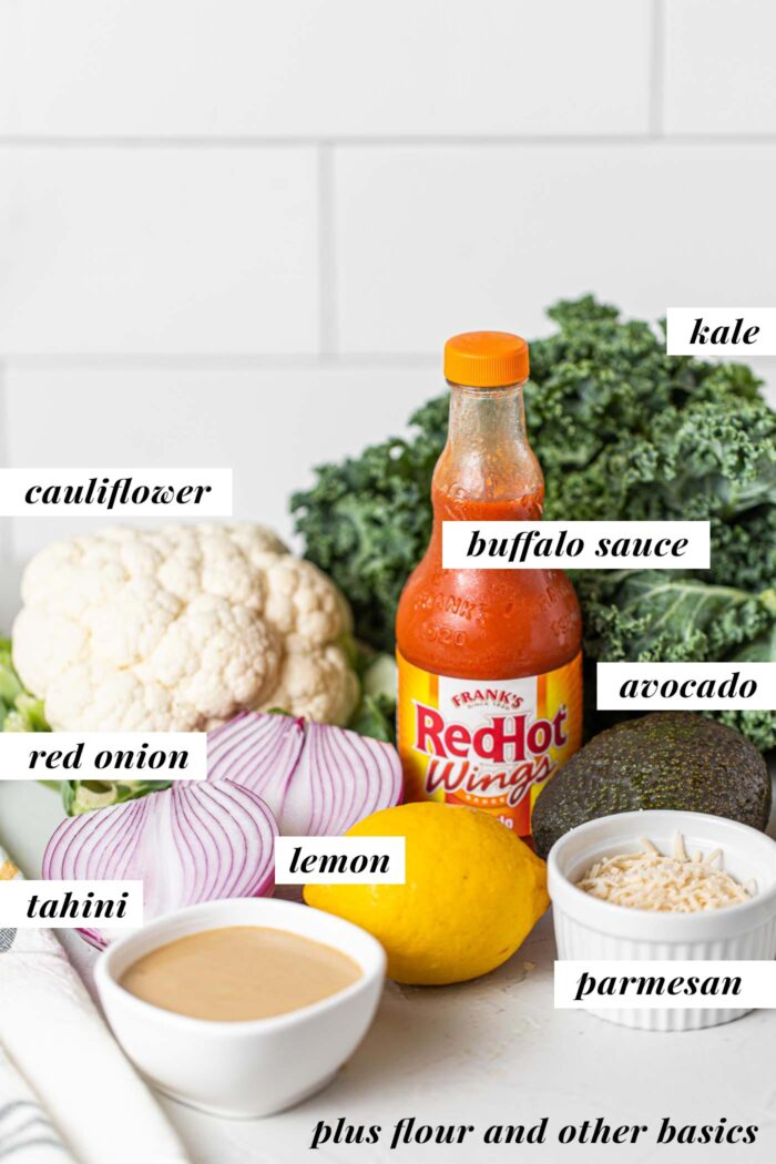 Tahini, avocado, kale, cauliflower, lemon, hot sauce and avocado on a counter.