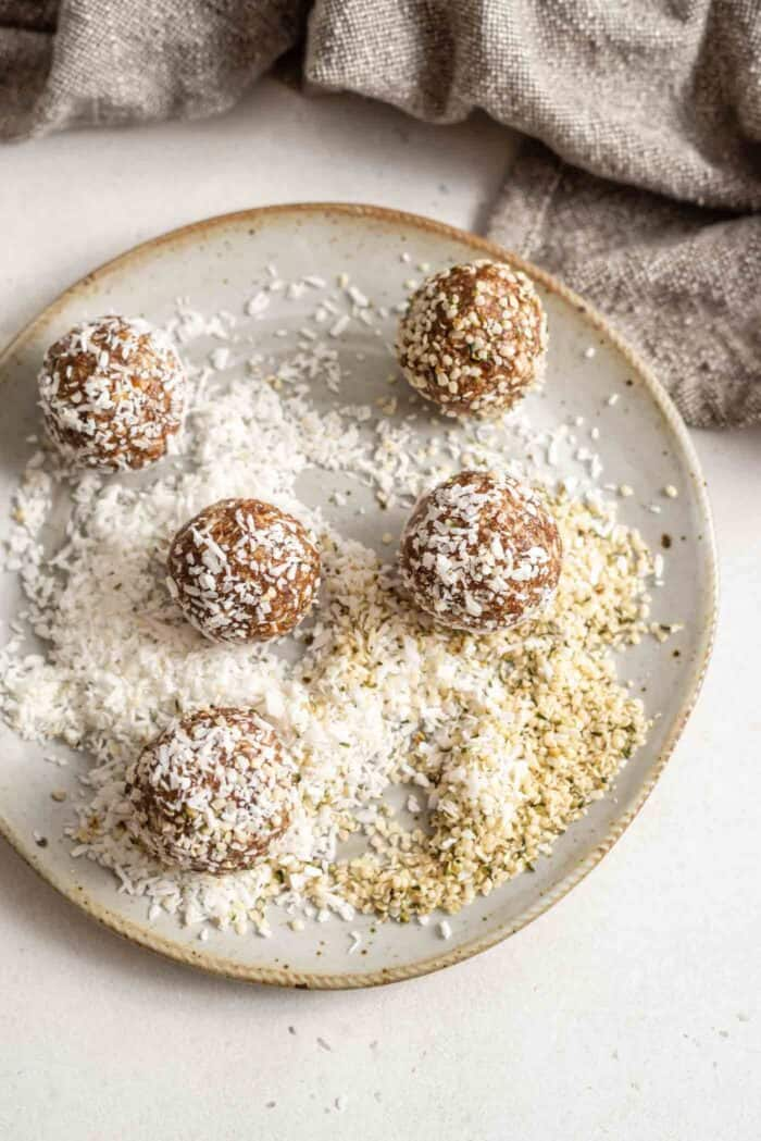 Energy balls being rolled in coconut and hemp seeds on a plate.