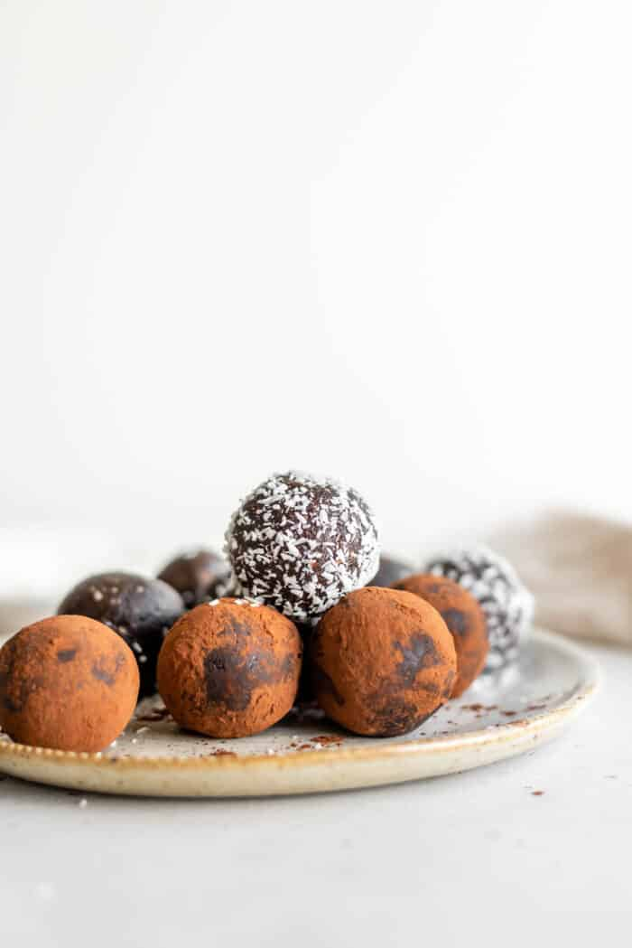 A plate of raw brownie balls rolled in cocoa powder and shredded coconut.
