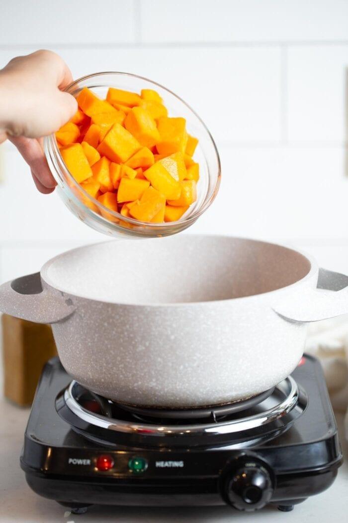 Dumping cubed butternut squash into a large pot.