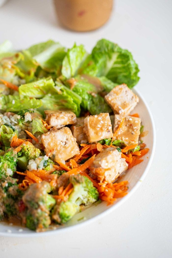 A close up of tofu in a bowl with lettuce, carrot, broccoli and peanut sauce.