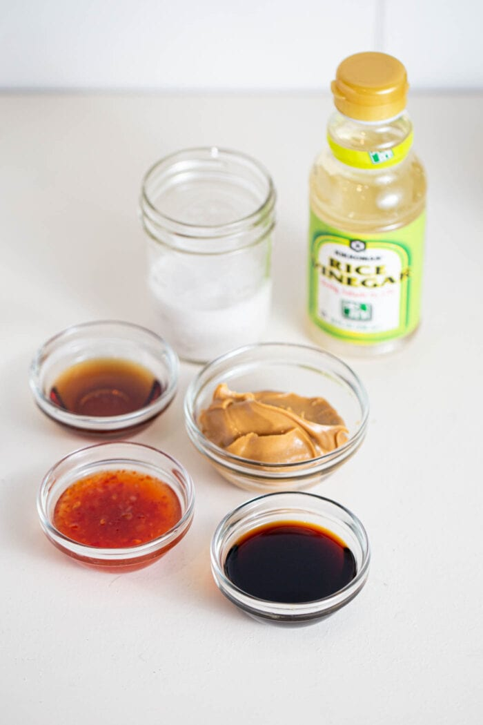 Various sauces in containers, coconut milk and rice wine vinegar on a counter.
