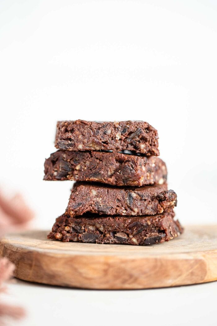 A stack of 4 raw brownies on a cutting board.