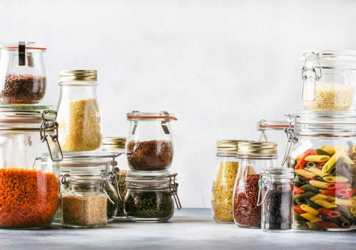 Various cereals, pasta, nuts and seeds in glass containers.