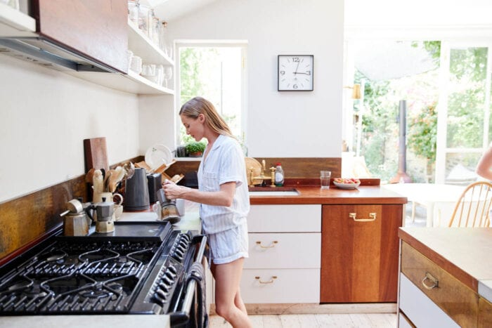 Women wearing pajamas in a kitchen and making fresh coffee.