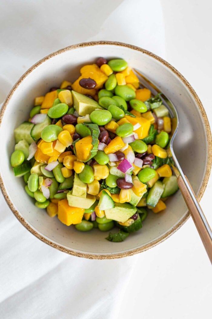 A overhead shot of a bowl of mango edamame salad.