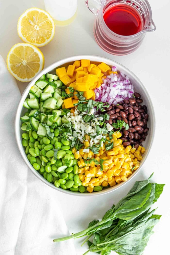 Edamame, corn, mango, black beans and cucumber in a large mixing bowl.