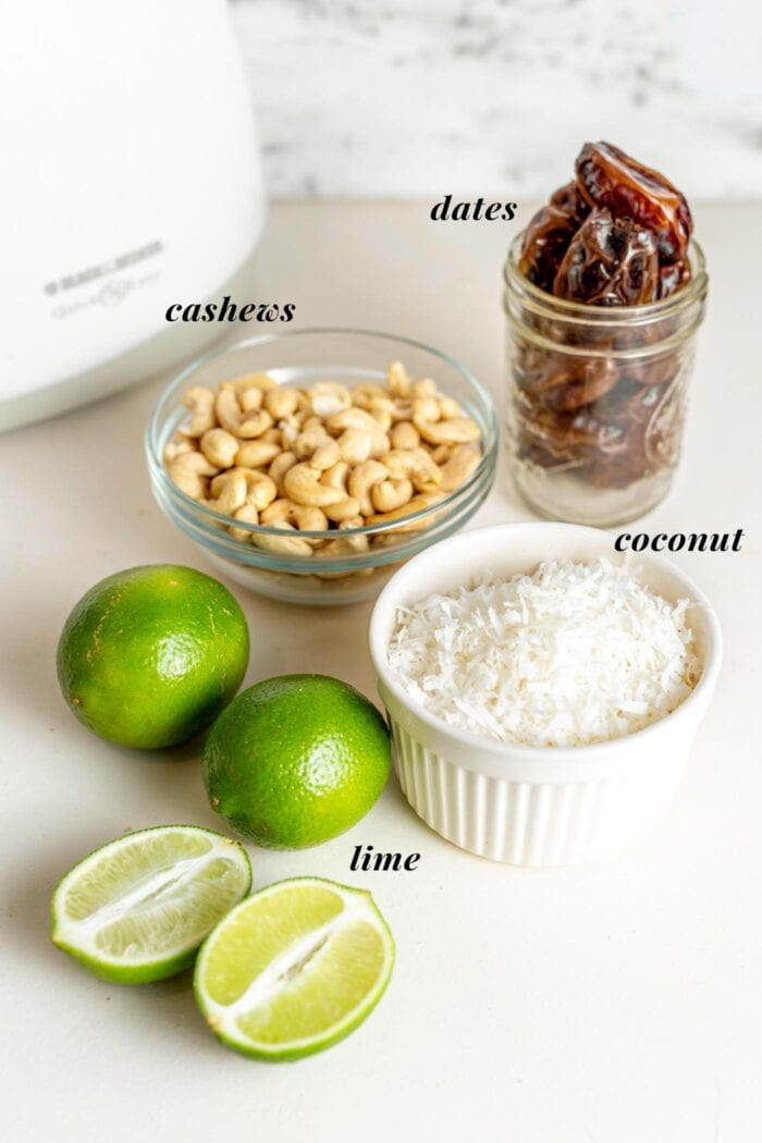 Lime, coconut, dates and cashews with labels on a counter.