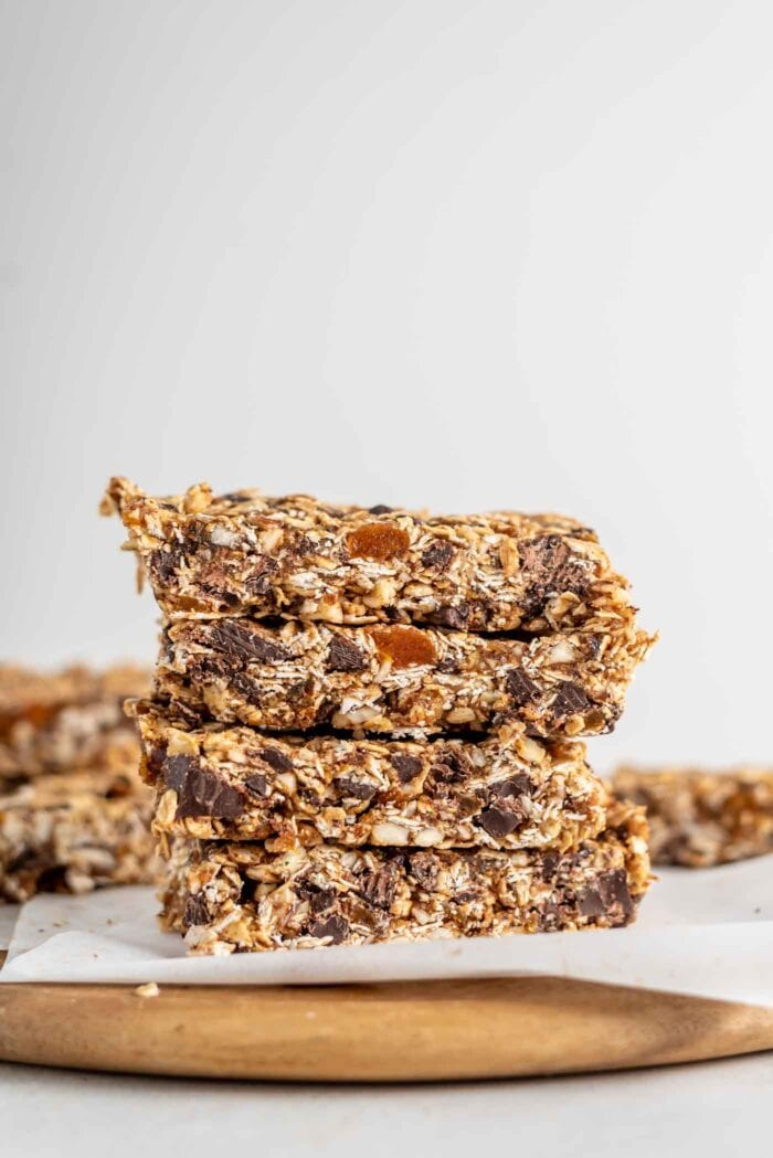 A stack of homemade granola bars on a cutting board.