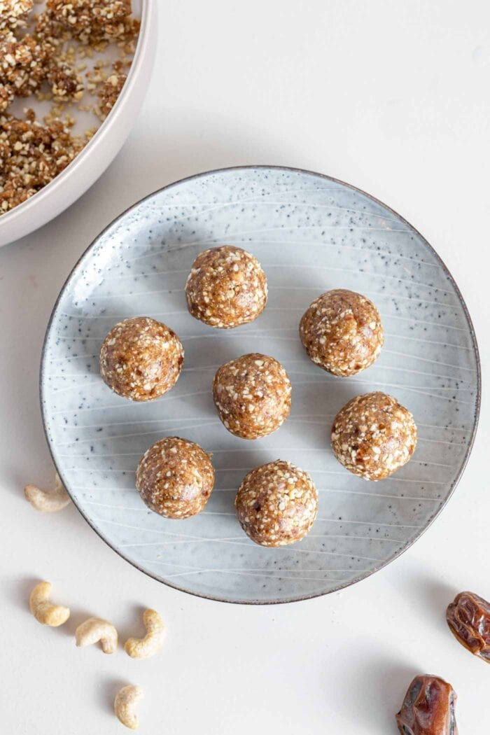 An overhead image of 7 raw energy balls on a plate.