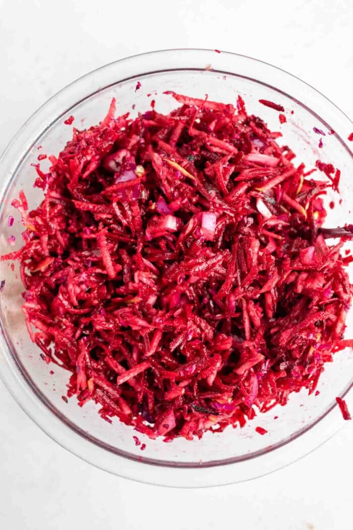 A raw beet, cabbage and apple salad in a bowl.