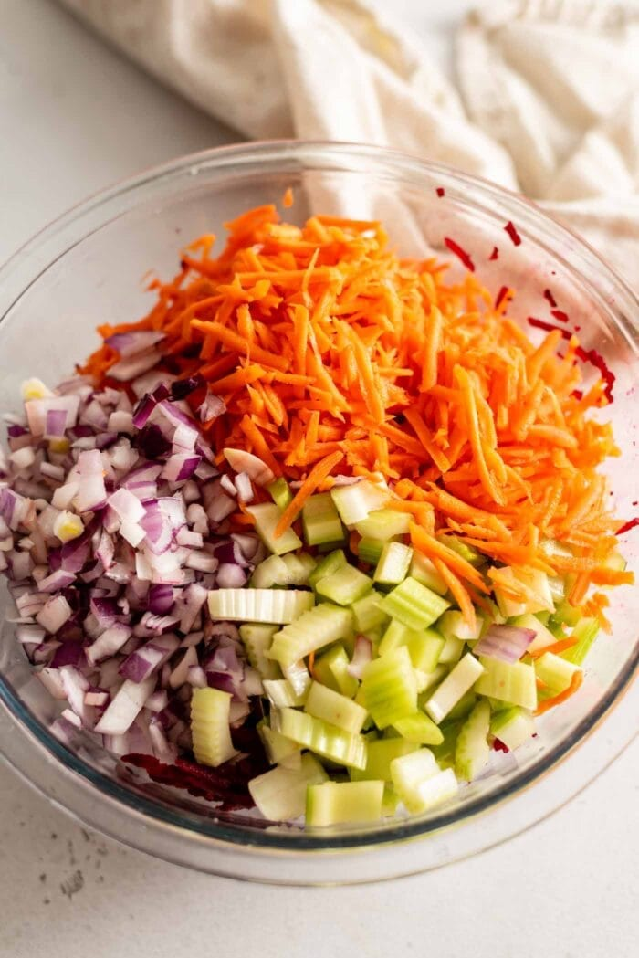 Chopped onion, carrot and celery in a glass mixing bowl.