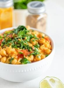 A close up of a bowl of chickpea rice stew topped with fresh cilantro.