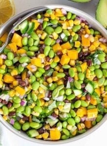 A large bowl of mango, corn, edamame and cucumber salad with a sliced avocado beside it.