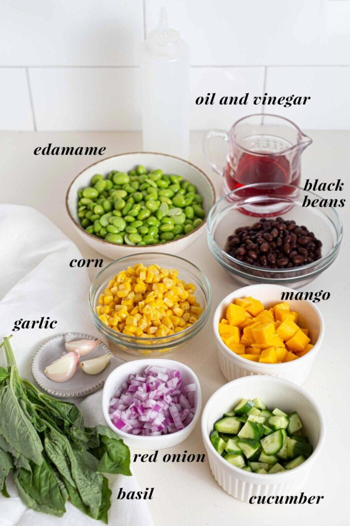 Various labelled ingredients for a mango edamame salad in bowls on a counter.