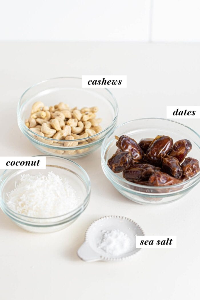 Dates, cashews, coconut and sea salt in small containers.