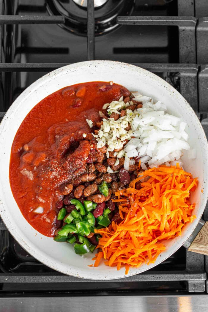 Tomato sauce, green pepper, onion, carrot and beans in a skillet.