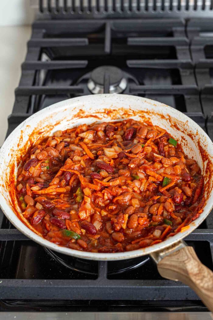 Cooked chili in a skillet on a gas range stove top.