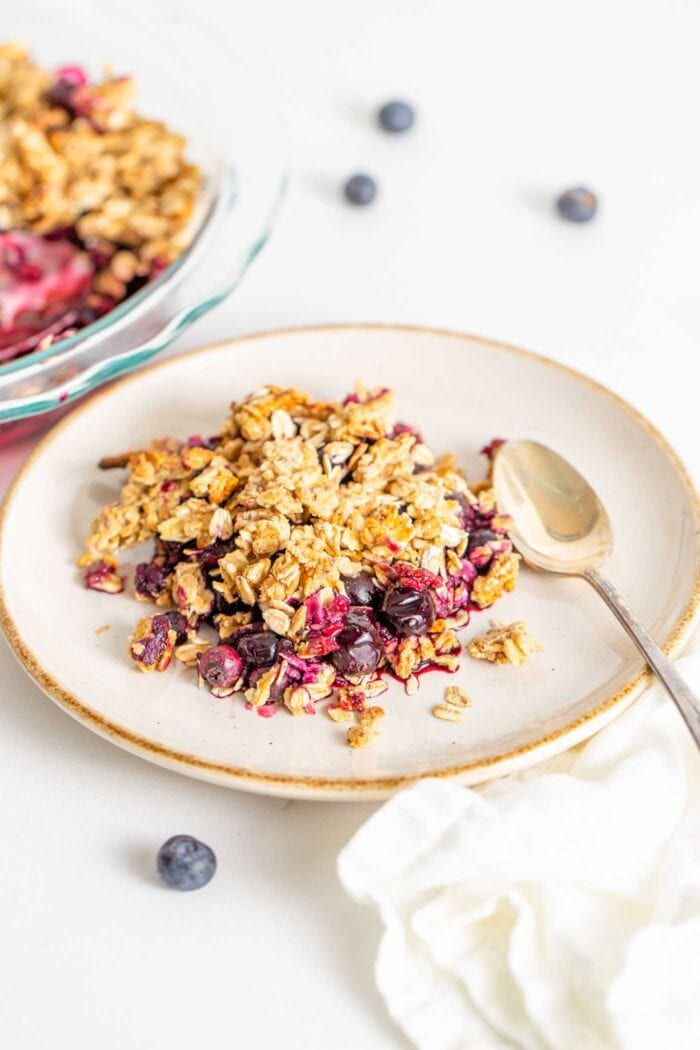 A serving of blueberry crisp on a plate with a spoon.