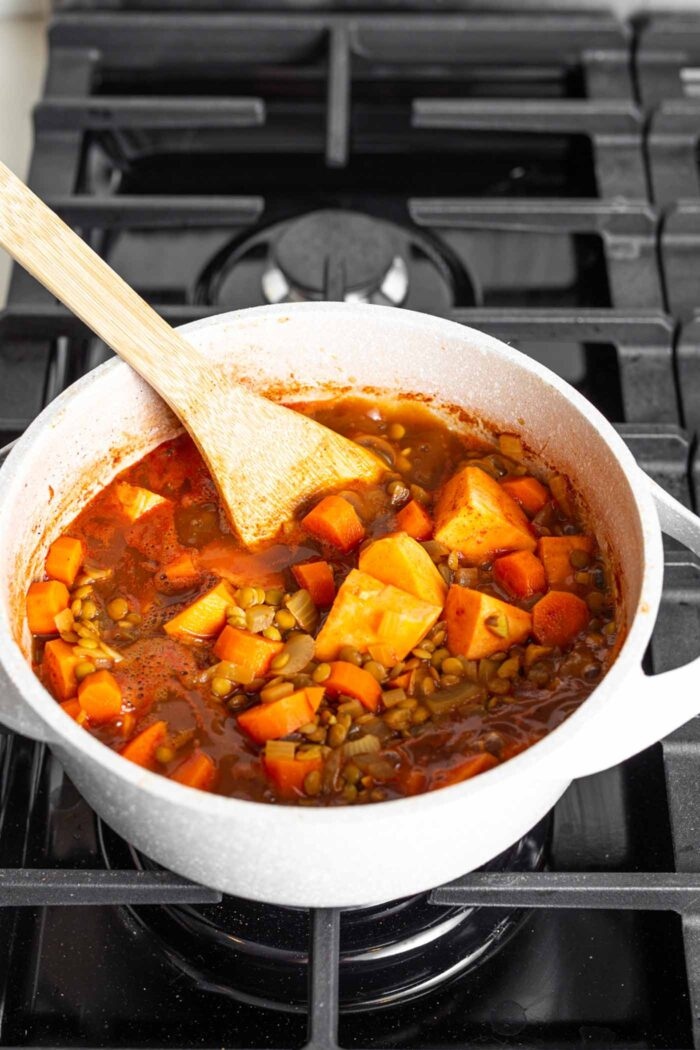 A thick tomato lentil stew cooking on a gas range stove.
