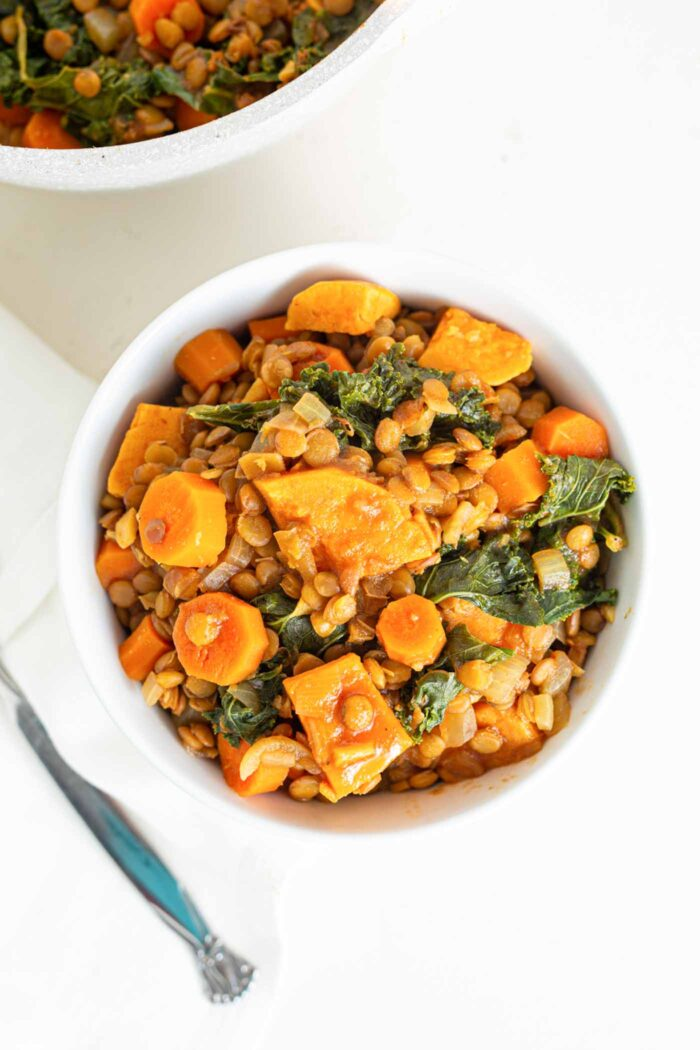 Overhead image of a bowl of sweet potato lentil stew with kale mixed into it.