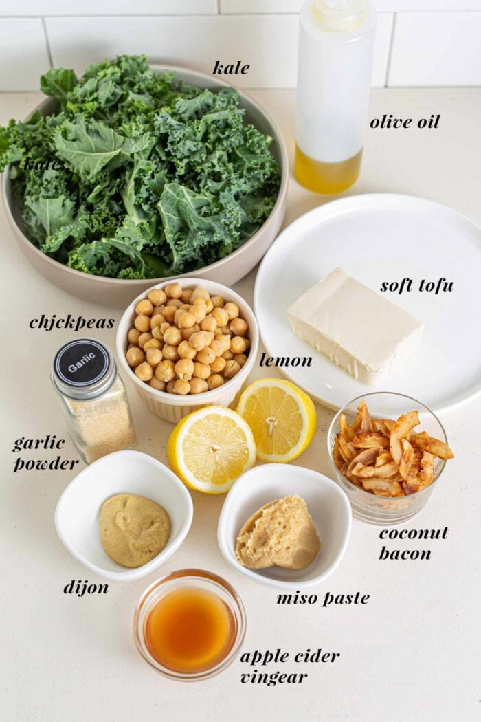 Labelled ingredients for a kale caesar salad on a counter top.