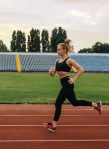 A fit woman in a sports bra and tights running on a track.