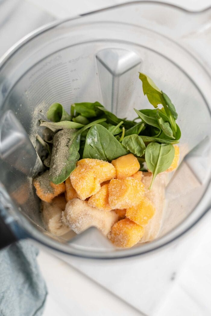 Mango, spinach and frozen banana in a Vitamix container.