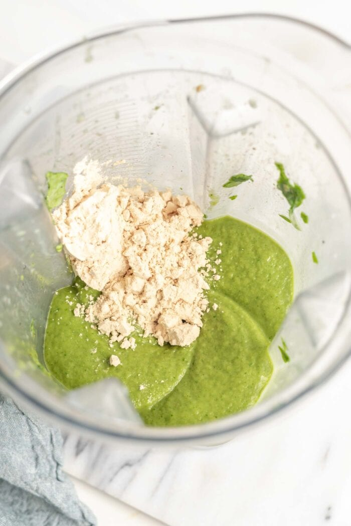 Protein powder added to a green smoothie in a Vitamix container.