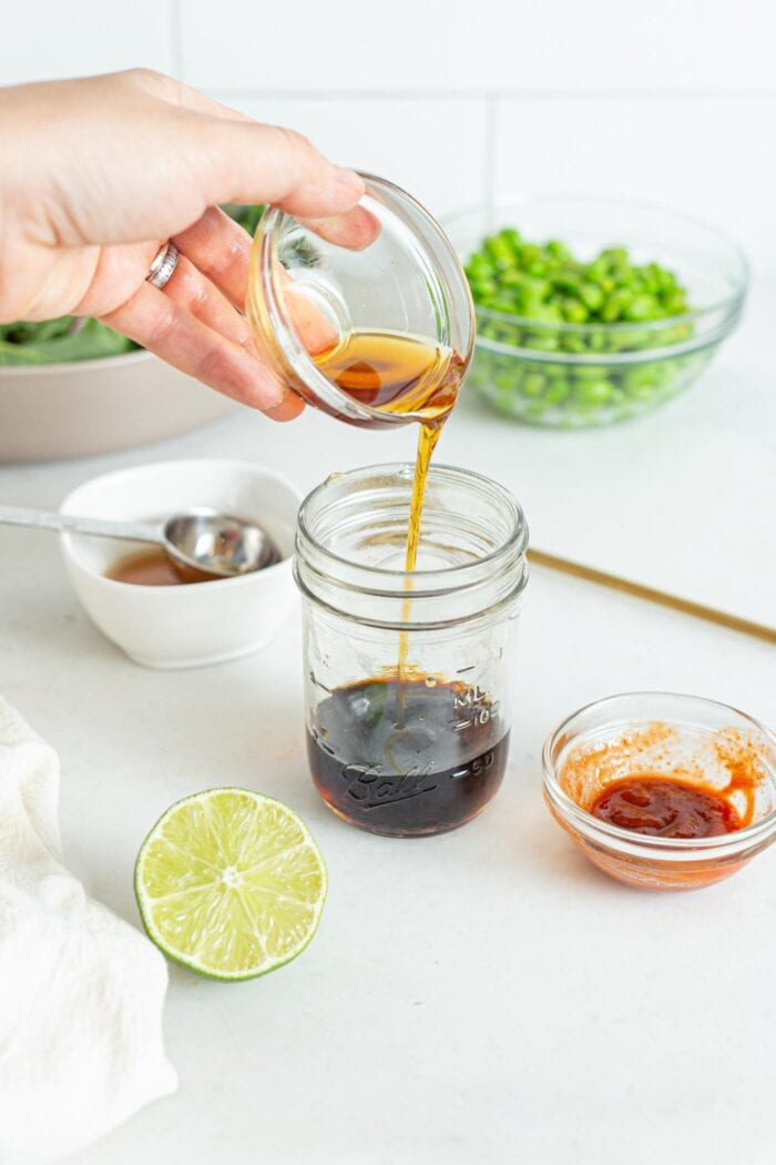 Pouring a small dish of maple syrup into a jar of soy sauce.