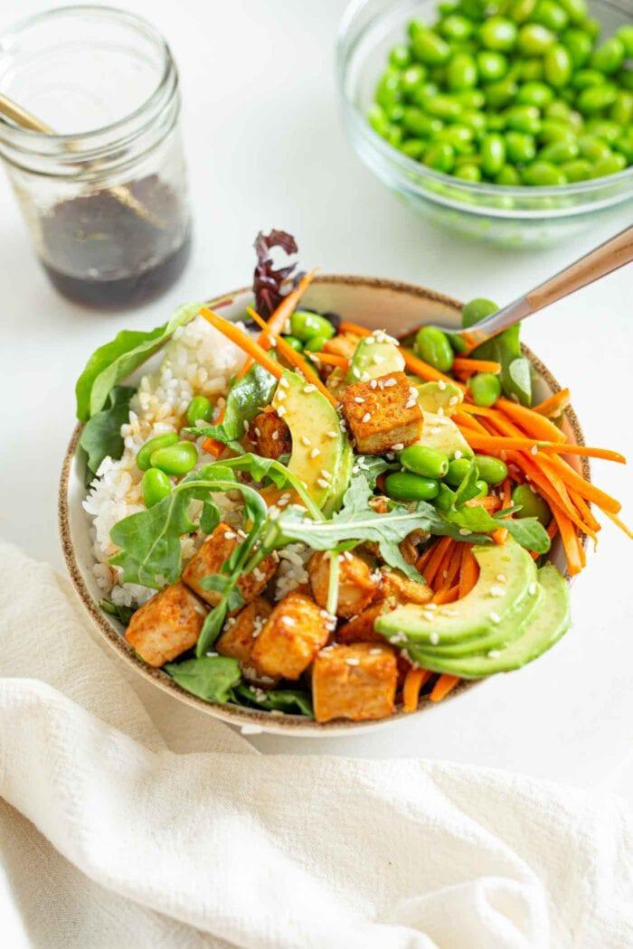 A buddha bowl with greens, avocado, tofu, carrot and edamame.