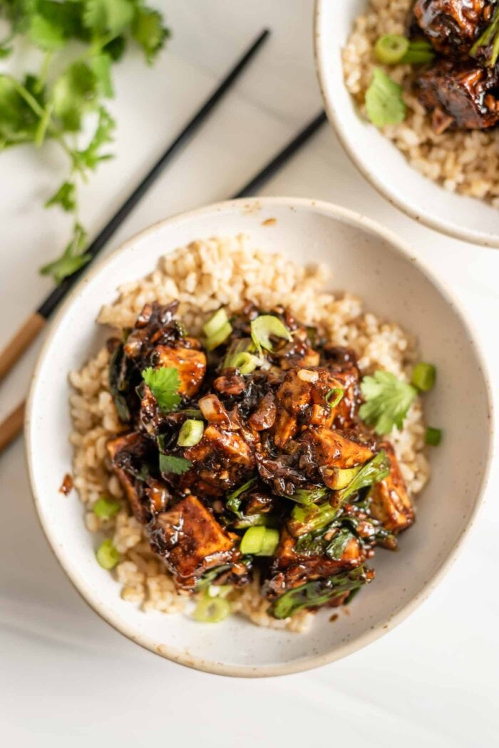 A bowl of tofu in black pepper sauce served over right and topped with sliced green onions.