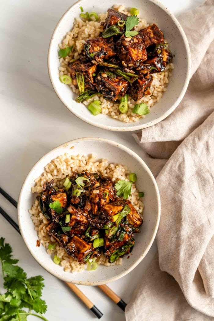 Two bowls of black pepper tofu with scallions served over rice.