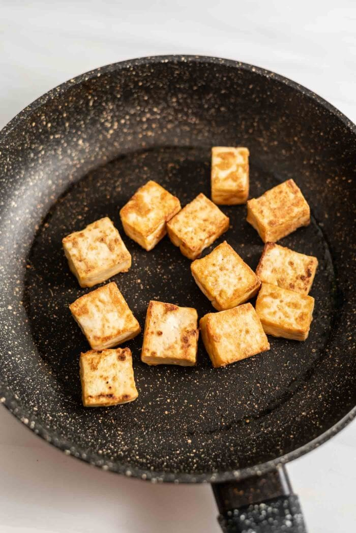 Browned, cubed tofu frying in a skillet.