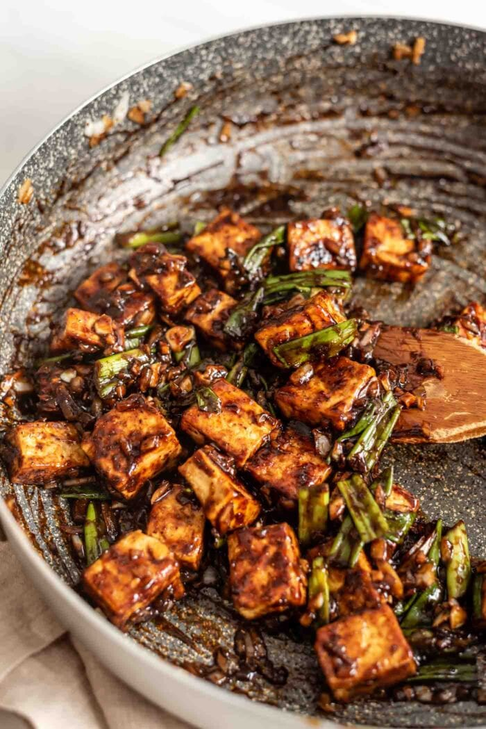 Tofu cooking in sauce with onions, garlic and ginger in a pan.