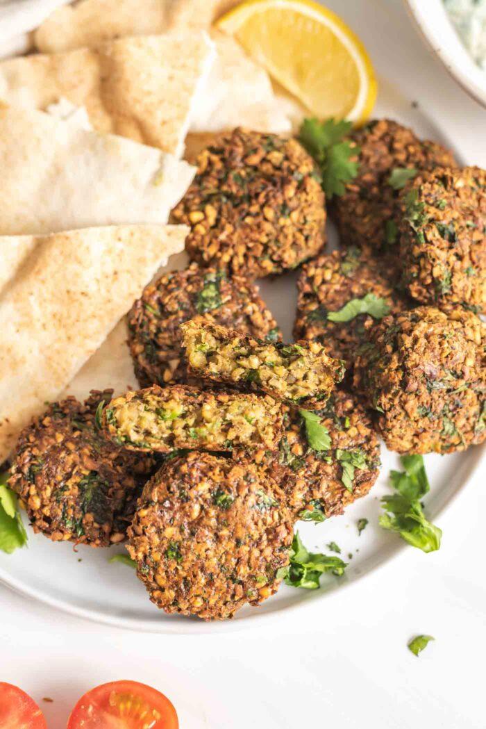 Crispy baked falafel on a plate, one is broken open to show inside.