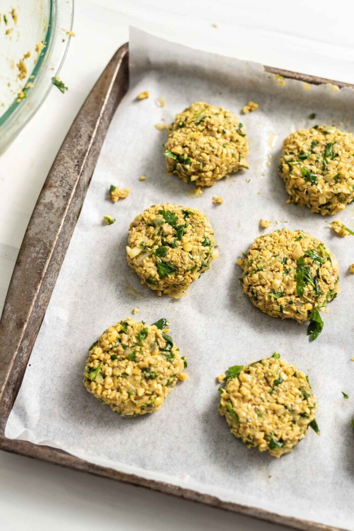 Raw falafel patties on a baking tray lined with parchment paper.