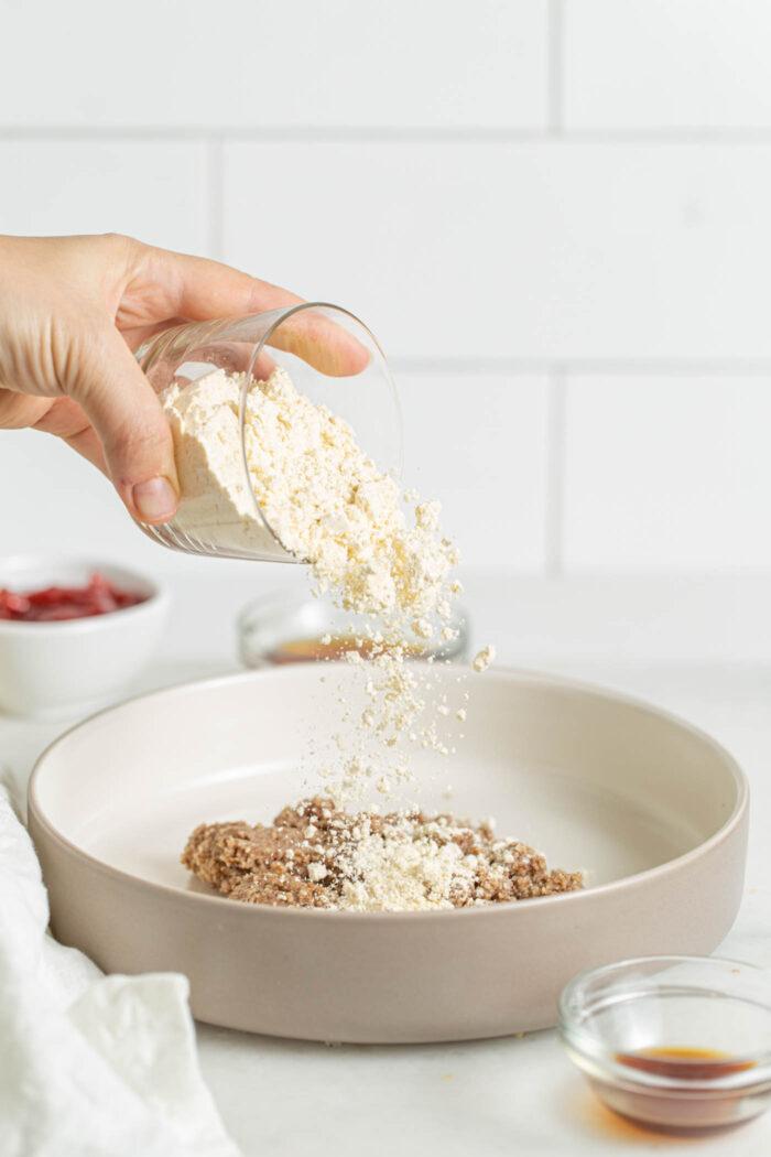 Adding flour to a mixing bowl of dough.