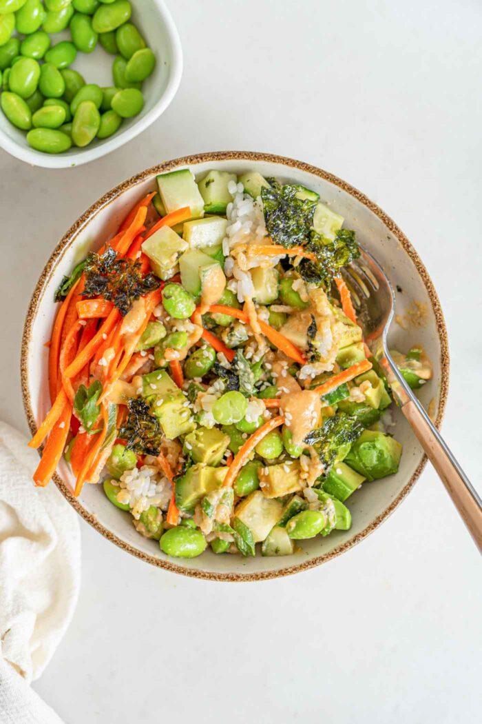 A rice bowl with edamame, carrot, avocado, cucumber and sauce.