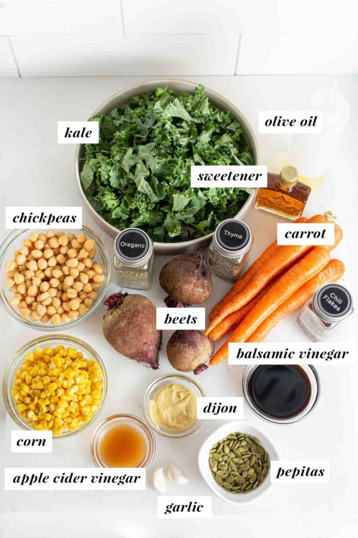 Various labelled ingredients in bowls and containers for a kale and beet salad.