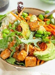A bowl with tofu, avocado, carrot, edamame and rice.