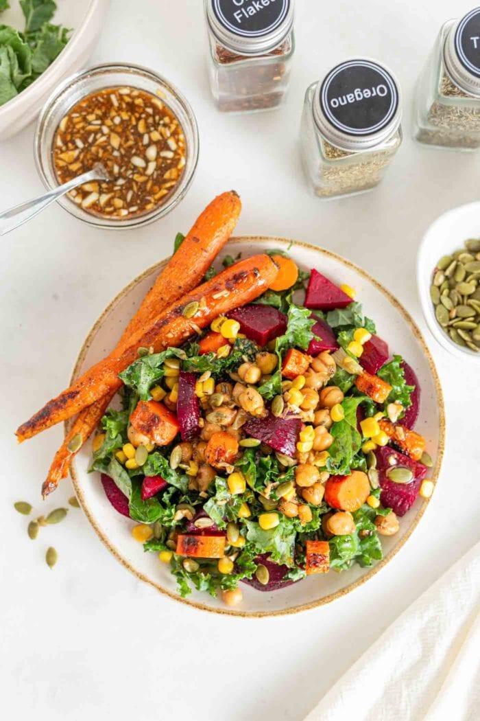 Bowl of kale salad with beet, corn, carrots and pumpkin seeds.