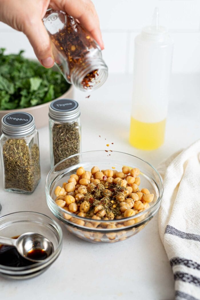 Adding chili flakes to a bowl of chickpeas.