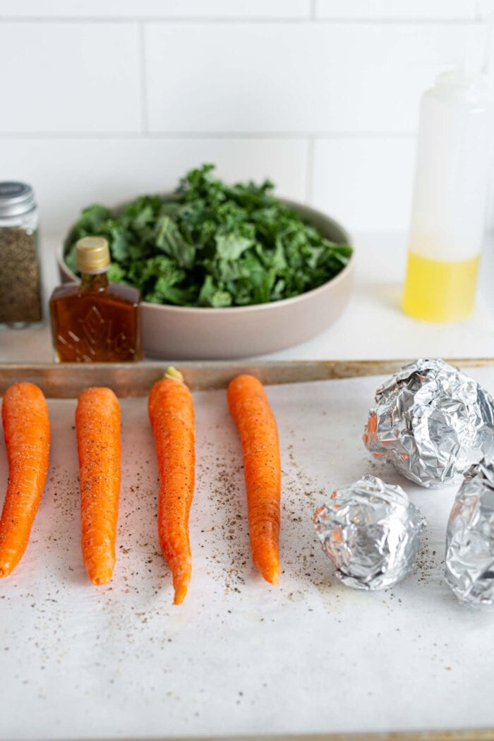 Whole carrots and foil wrapped beets on a baking tray lined with parchment paper.