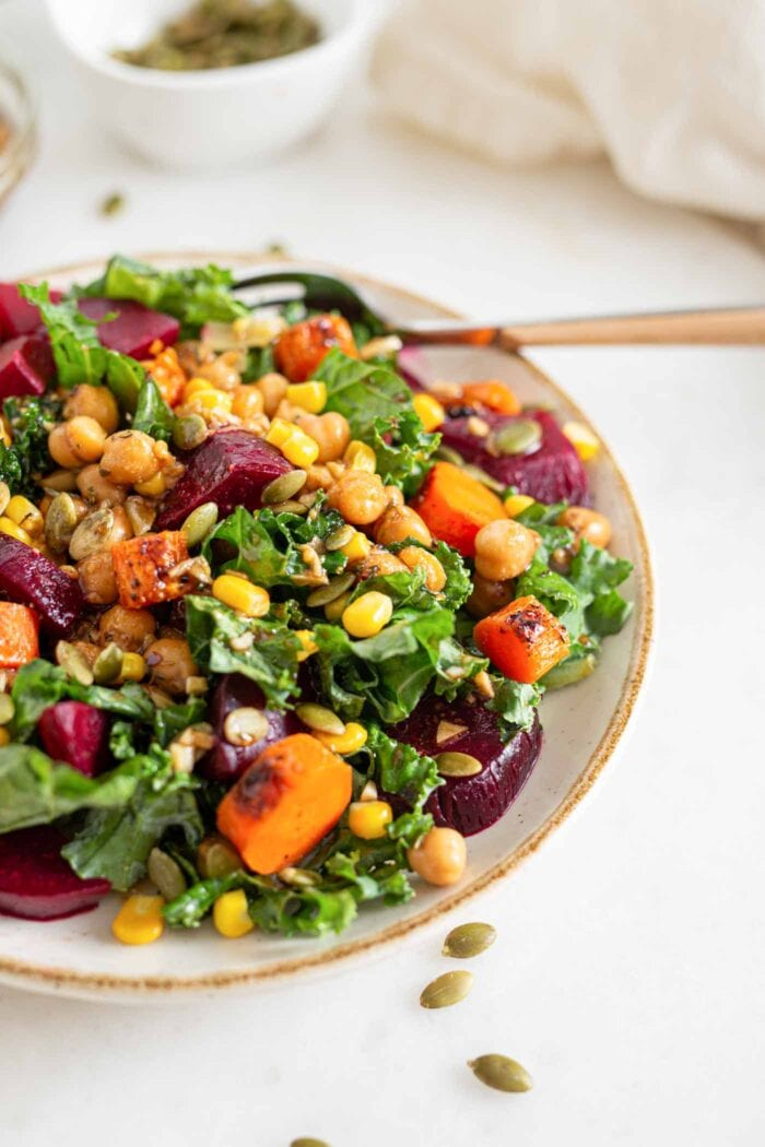 Bowl of kale salad with chickpeas, carrots, beets and corn.