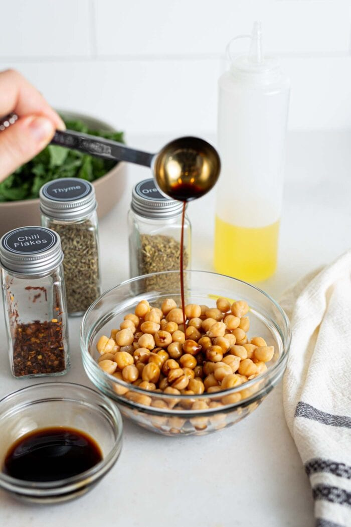 Pouring balsamic vinegar into a bowl of chickpeas.