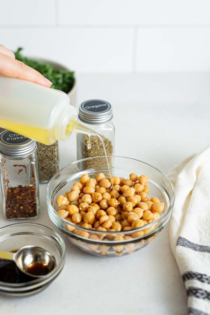 Pouring olive oil over a bowl of chickpeas.